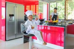 Intymny Tajlandzki szefa kuchni kucharstwo, jego mały syn w szefa kuchni ` s kapeluszowy niedaleki s Obrazy Stock
