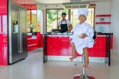 Intymny Tajlandzki szefa kuchni kucharstwo, jego mały syn w szefa kuchni ` s kapeluszowy niedaleki s Zdjęcia Royalty Free
