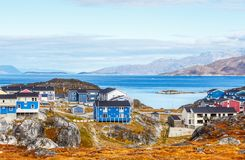 Inuit houses and cottages in residential district of Nuuk city with fjord and mountains in the background, Greenland. Appartments architecture arctic autumn royalty free stock photo