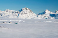 Inuit village and mountains, Greenland. An inuit village in a snowy landscape stock photos