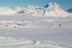 Inuit village and mountains, Greenland. An inuit village in a snowy landscape stock photo