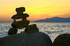 Inukshuk. Traditional native rock statue on a Vancouver beach at sunset. Symbol of the 2010 Vancouver Olympics Royalty Free Stock Photos