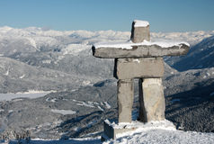 Inukshuk. An Inukshuk (symbol of the 2010 winter olympic games and a traditional native sculpture) stands on Whistler mountain overlooking Blackcomb mountain Royalty Free Stock Image