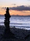 Inukshuk apedreja a estátua na costa no por do sol, Jordan River, BC Fotografia de Stock Royalty Free