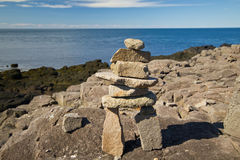 Inukshuk on coast. Wide angle view of a stone land mark over looking the rocky coastline of Bay of Fundy,brier island,Nova Scotia.The sky and ocean are blue Royalty Free Stock Photo