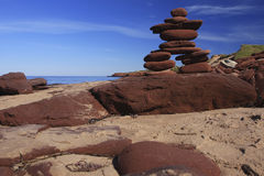 Inukshuk fêz de rochas vermelhas Fotos de Stock Royalty Free