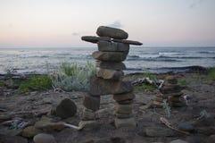 Inukshuk från indiankultur som framme står av havet royaltyfria bilder