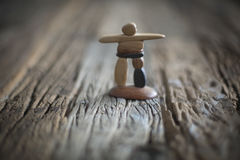 Inukshuk-Inuit Art. Inukshuk on wooden table. Inuit art. Sculpture Royalty Free Stock Photo