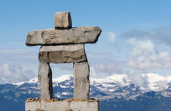 Inukshuk - inuit symbol for 'the way'. Giant rock inukshuk with mountains - inuit symbol for 'the way' & the 2010 winter olympics Stock Photography