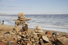 Inukshuk or Inuksuk on a rocky beach with ice on the ocean in late June in the high arctic. Near the community of Cambridge Bay Stock Photo