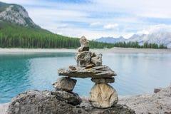 Inukshuk nahe dem See umgeben durch Berge Alberta Canada Stockbild