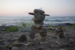 Inukshuk from Native American culture standing in front of the sea royalty free stock images