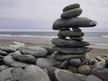 INUKSHUK_NOVA SCOTIA. A inukshuk of beach stones is seen at Lawrencetown Beach in Nova Scotia in June 2016. Traditionally the inuksuk may have been used as Stock Photo