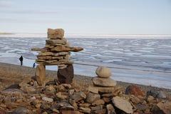 Inukshuk ou Inuksuk sur une plage rocheuse avec de la glace sur l'océan fin juin dans le haut Arctique Images libres de droits