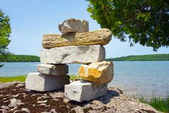 Inukshuk over looking a lake. Stock Images
