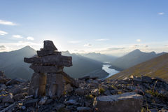 Inukshuk rock sculpture at the summit of a hiking trail royalty free stock photos