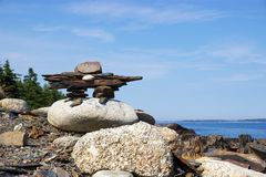 Inukshuk on rocky Nova Scotia, Canada coastline. An inukshuk or inuksuk, also known as an inunnguaq when it takes the form of a human, is a stone marker Stock Photos