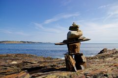 Inukshuk on rocky Nova Scotia, Canada coastline. An inukshuk or inuksuk, also known as an inunnguaq when it takes the form of a human, is a stone marker Stock Photography