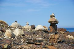 Inukshuk on rocky Nova Scotia, Canada coastline. An inukshuk or inuksuk, also known as an inunnguaq when it takes the form of a human, is a stone marker Stock Image