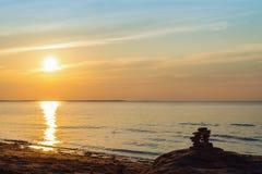 Inukshuk stones on ocean shore at sunset Stock Image