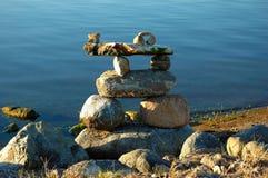 Inukshuk on water edge. Stone inukshuk on edge of calm water Stock Photo