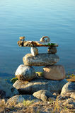 Inukshuk on water edge. Stone inukshuk on edge of calm water Stock Image