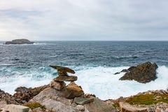 Inukshuk y resaca en la costa de Terranova foto de archivo