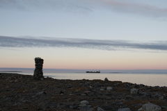 Inuksuk along arctic shore with barge in background. Near Hudson Bay Royalty Free Stock Image
