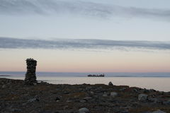 Inuksuk along arctic shore with barge in background. Inuksuk or Inukshuk along arctic shore with barge in background on the Hudson Bay Royalty Free Stock Photos