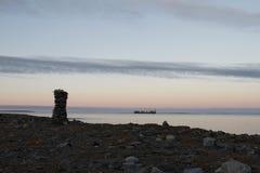 Inuksuk entlang arktischem Ufer mit barge herein Hintergrund Lizenzfreies Stockbild