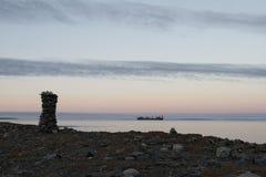 Inuksuk entlang arktischem Ufer mit barge herein Hintergrund Lizenzfreie Stockfotos