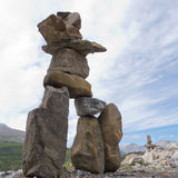 Inuksuk large stacked stones cairn trail marker. Large rocks stacked and balanced to form an Inuksuk stone landmark or cairn as a marker or monument in Stock Photography
