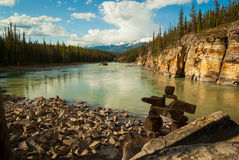An Inuksuk Man at the Edge of the Athabasca River. A tranquil view of the Athabasca River in Jasper National Park Stock Images