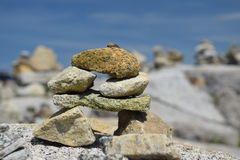 Inuksuk. On rock with other  in background Stock Photography