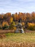 Inuksuk stone sculpture wearing witch hat. Inuksuk stone sculpture wearing witch hat and holding the broom in front of autumn forest Stock Photography