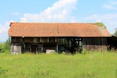 Inutilizzato ha abbandonato il granaio di legno con spazio aperto nei bordi medi e dilapidati circondati con alta erba non taglia immagine stock
