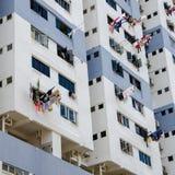 Invånare i en höghuslägenhet att använda långa poler för att torka kläder royaltyfri foto