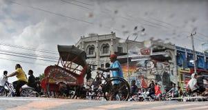 Invånare som cyklar längs den huvudsakliga gatan av staden av soloen Arkivfoton