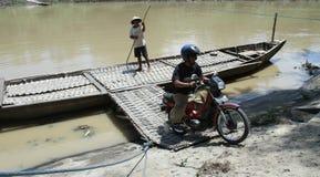 Invånare som korsar floden med fartyget kanotar solo, som hjälpmedel av korsningen till och från solo centrala Java Indonesia Arkivfoto