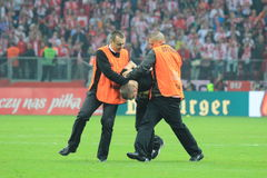 Invader. WARSAW, POLAND - OCTOBER 11, 2014: Stewards stops pitch invader after entering the field during the UEFA EURO 2016 qualifying match of Poland vs Royalty Free Stock Photo