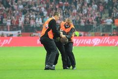 Invader. WARSAW, POLAND - OCTOBER 11, 2014: Stewards stops pitch invader after entering the field during the UEFA EURO 2016 qualifying match of Poland vs Royalty Free Stock Photography