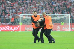 Invader. WARSAW, POLAND - OCTOBER 11, 2014: Stewards stops pitch invader after entering the field during the UEFA EURO 2016 qualifying match of Poland vs Royalty Free Stock Image