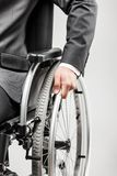 Invalid or disabled businessman in black suit sitting wheelchair stock image