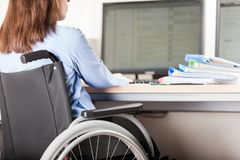 Invalid or disabled woman sitting wheelchair working office desk computer Stock Image