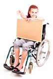 Invalid girl on wheelchair with cork board showing something Stock Photography