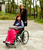 Invalid girl on the wheelchair with helper Royalty Free Stock Photo