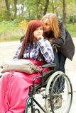 Invalid girl on the wheelchair with helper Royalty Free Stock Images