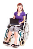 Invalid girl on wheelchair with laptop Royalty Free Stock Photo