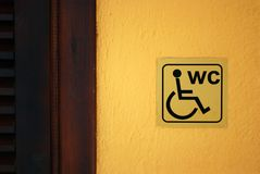 WC Label. Invalid Lavatory Label on the Yellow Wall near the Door Royalty Free Stock Image