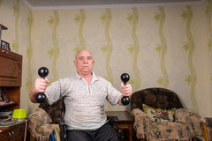 Invalid old man doing exercises with dumbbells Stock Photo